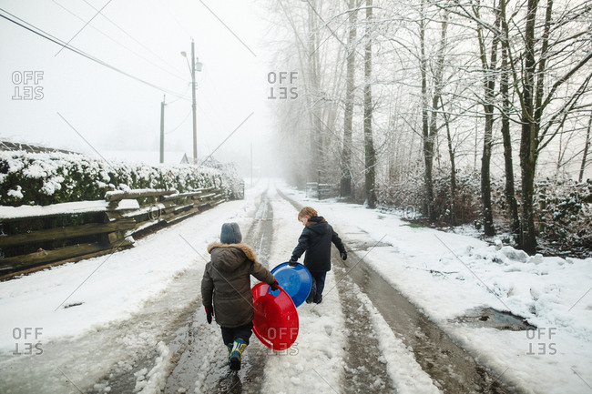 Two kids walking down snowy street with sleds