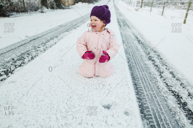 Toddler girl sitting on snowy street