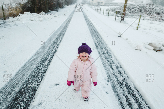 Toddler girl standing on snowy street