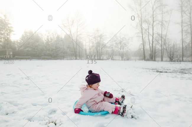 Toddler girl sledding in snowy field
