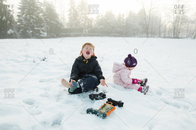 Two kids sitting together in snowy field