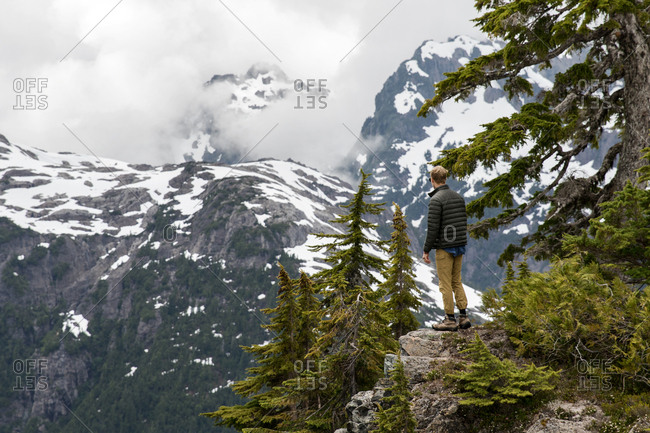 Man looking out at snowy mountains on Vancouver Island, British Columbia, Canada