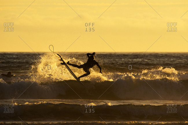 A surfer riding a wave about to fall from board