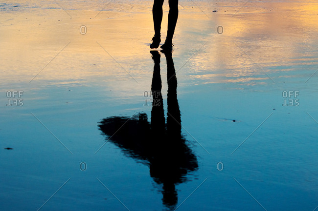 Reflection of surfer silhouette holding a board