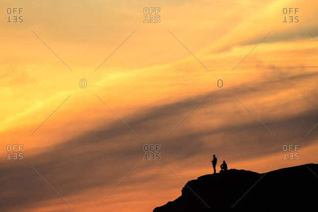 Silhouette of two men on a mountain at sunset