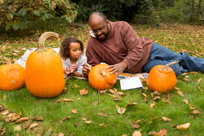 Father helping his daughter carve pumpkins