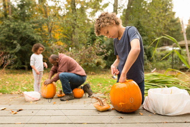 Father carving pumpkins with his two kids