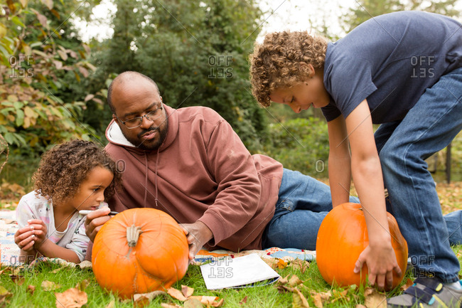 Father helping his kids carve pumpkins