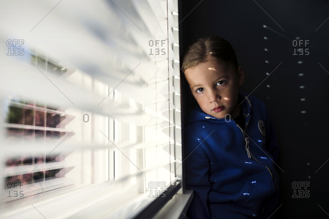 Boy leaning against wall in light from window blinds