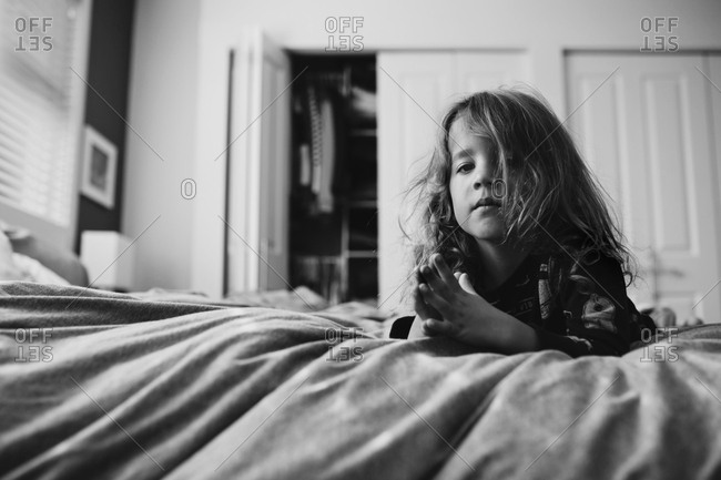 Boy with folded hands leaning against bed