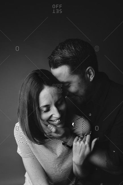 Man embracing and nuzzling smiling woman