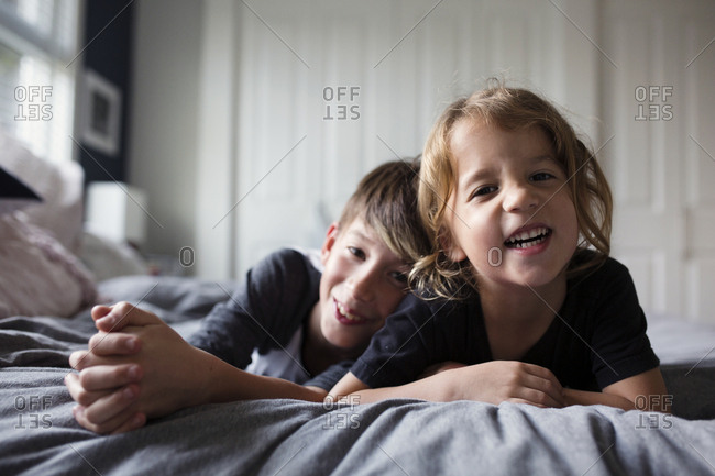 Brothers laughing together while lying on bed