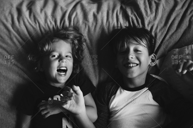 Brothers laughing together while lying down on bed