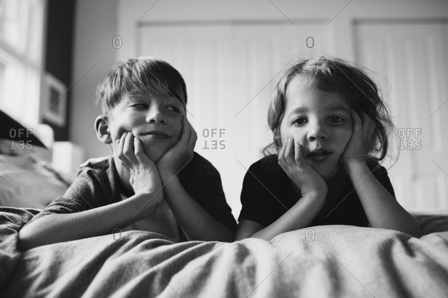 Two brothers with hands on chin lying on bed together