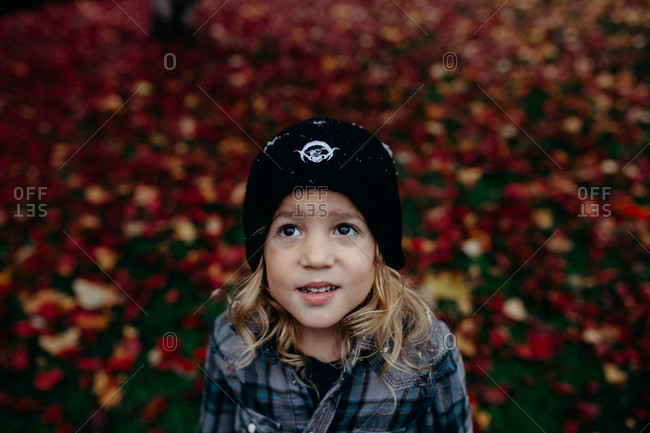 Boy wearing a knit hat and flannel shirt looking up