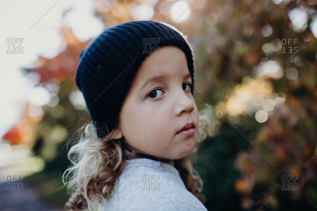 Portrait of a boy with long curly hair wearing a knit hat