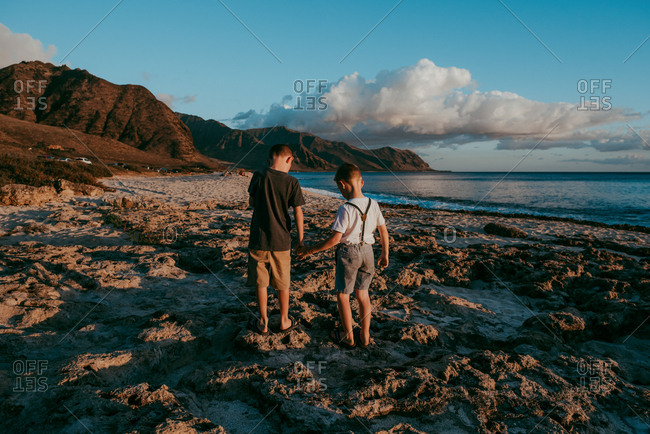 Boys walking on rocks and sand by ocean