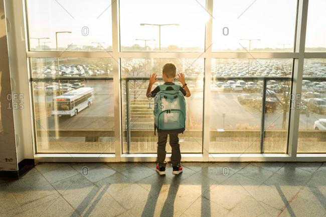 Boy with blue backpack looking out airport window