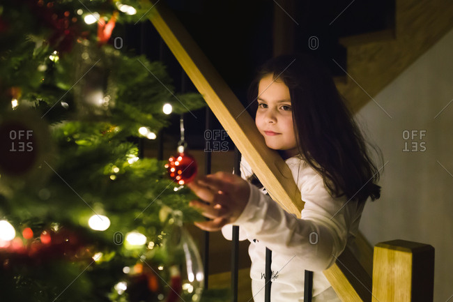 Little girl touching red ornament on a Christmas tree
