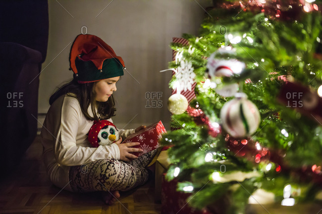 Little girl wearing elf hat holding a present