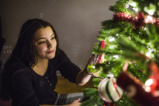 Girl touching ornament on a Christmas tree