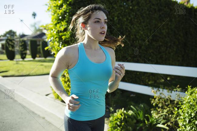 Young woman jogging in suburban neighborhood