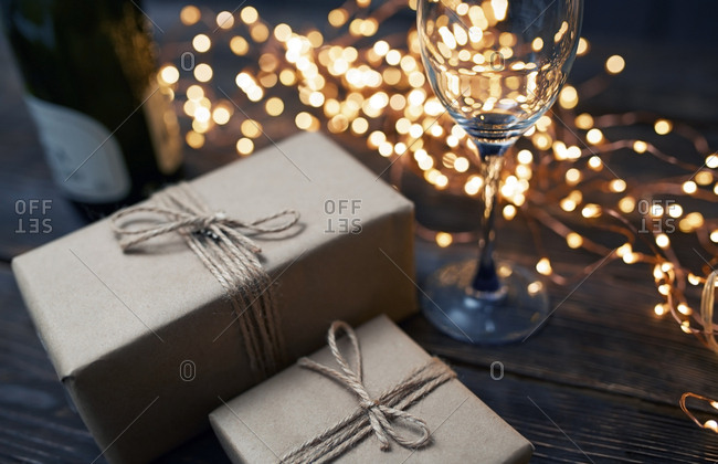 Gift boxes and Christmas light on a table with wineglass and bottle