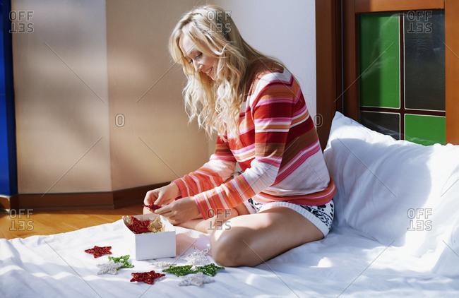 Woman at home preparing Christmas ornament