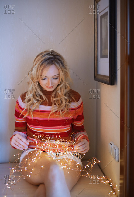 Woman sitting on the table and holding Christmas light