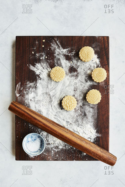 Mooncake cookies cut-outs on wooden cutting board with flour and rolling pin