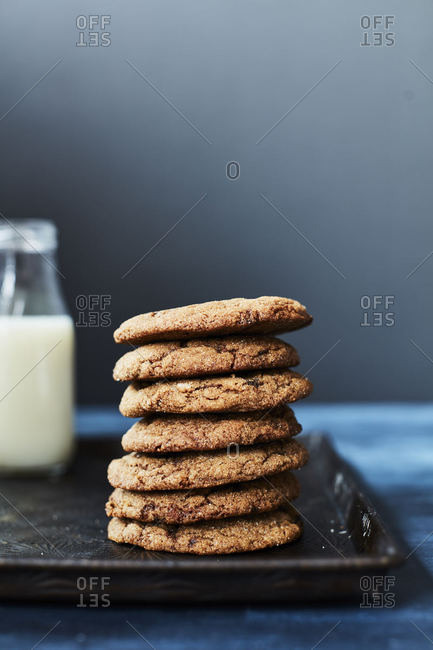 Stack of cookies on a tray with milk in background