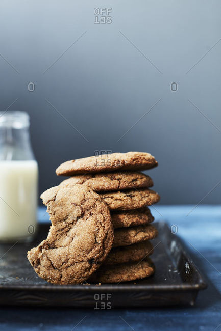 Stack of cookies and one missing a bite on a tray with milk in background