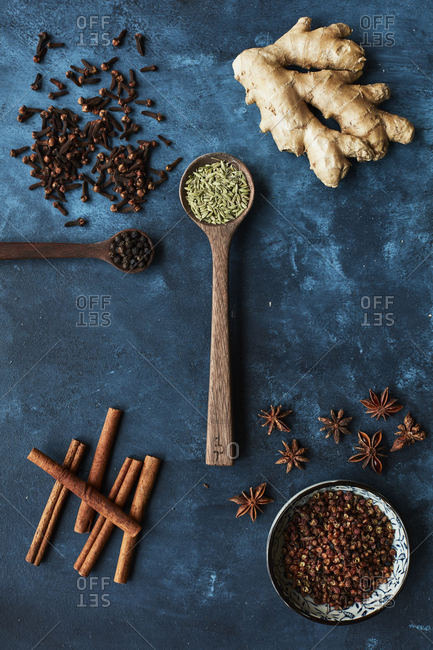 Overhead view of a variety of spices on a blue background