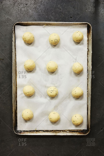 Dough balls with poppy seeds on a baking tray