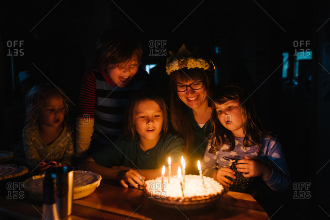 Family surrounding birthday pie with candles