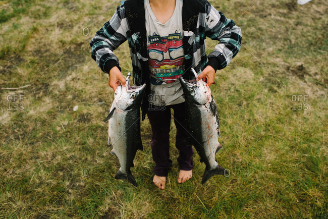 Young boy holding two large freshly caught fish