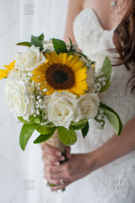 Bride holding bouquet of white roses and sunflowers
