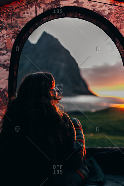 Unrecognizable woman wrapped up in blanket sitting in tent and enjoying beautiful sunset