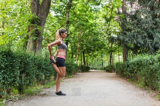 Young fit woman in sportswear training alone on pathway in green park stretching legs