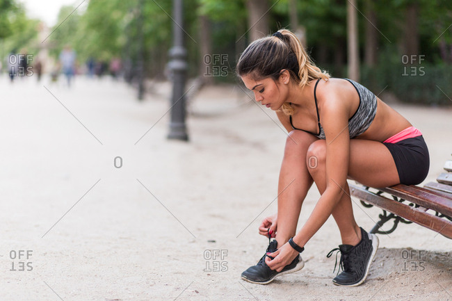 Young fit model in sportswear sitting on bench and tying shoelaces on background of park