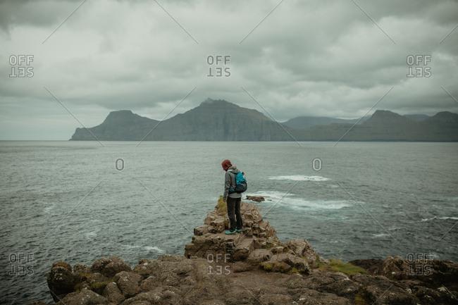 Traveler on rocks of ocean