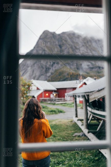 Unrecognizable woman in orange jumper standing near boat shed in mountain village and enjoying view