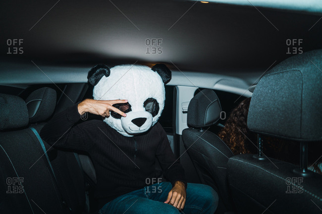 Man in panda mask sitting on back seat of car and showing peace gesture