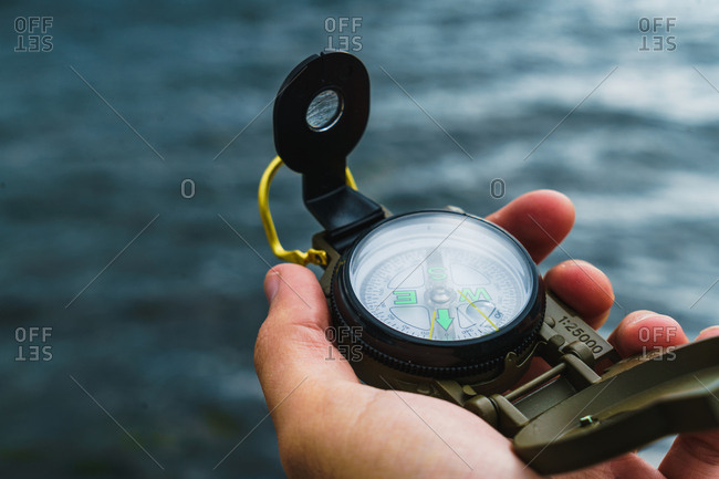 Crop male hand holding compass