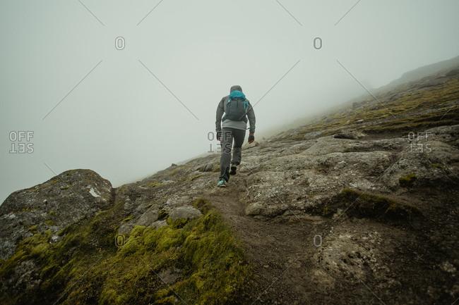 Man walking on rocky green slope of hill