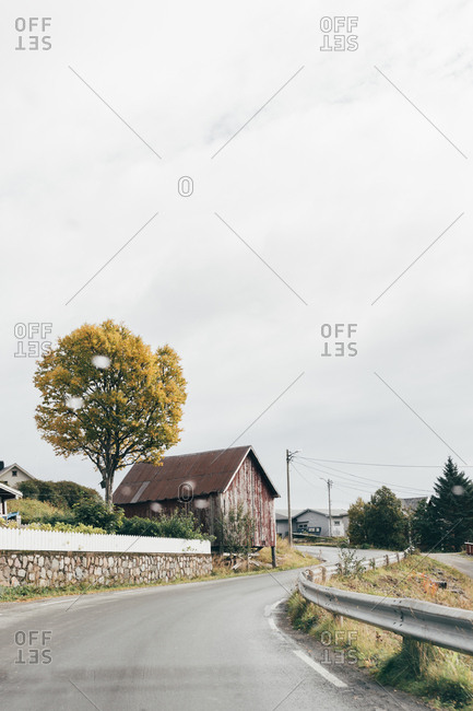 Narrow asphalt road going through small village on gray day