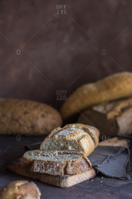 Various types of home-made bread on rustic table