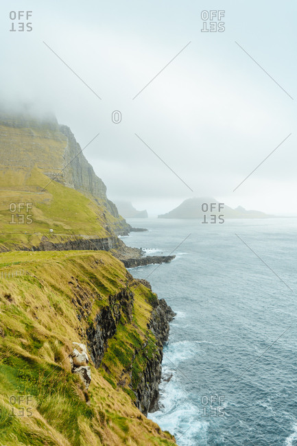 Huge cliffs above rough ocean