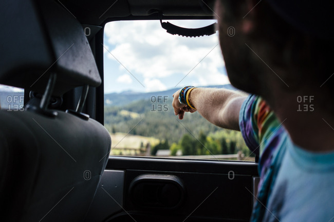 Man pointing at scenic view out of car window