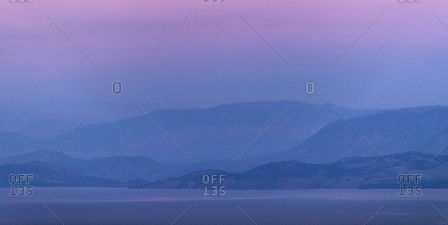 Mountains at sea in hazy sunset. Corfu, Greece